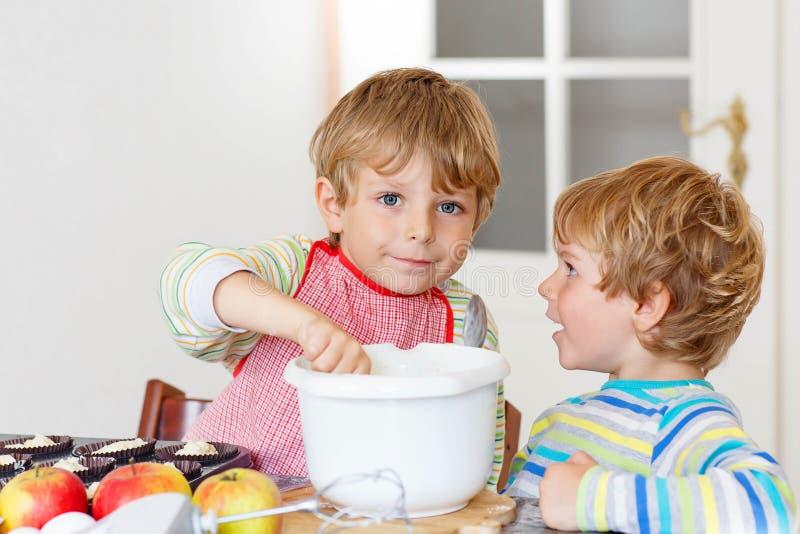 Zwei Kleinkindjungen, die zuhause Apfelkuchen backen lizenzfreie stockfotos