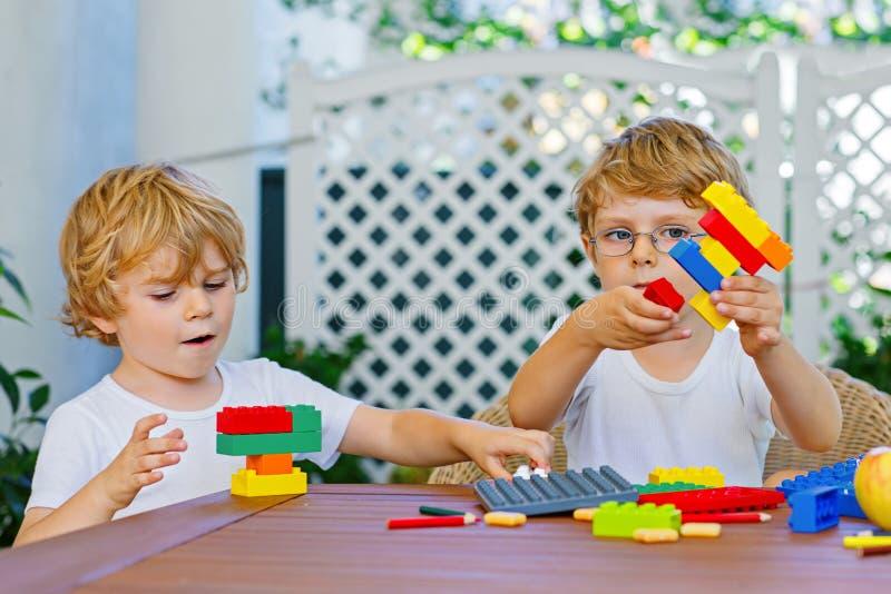 Zwei Kleinkindjungen, die zusammen mit Plastikblöcken spielen stockfoto