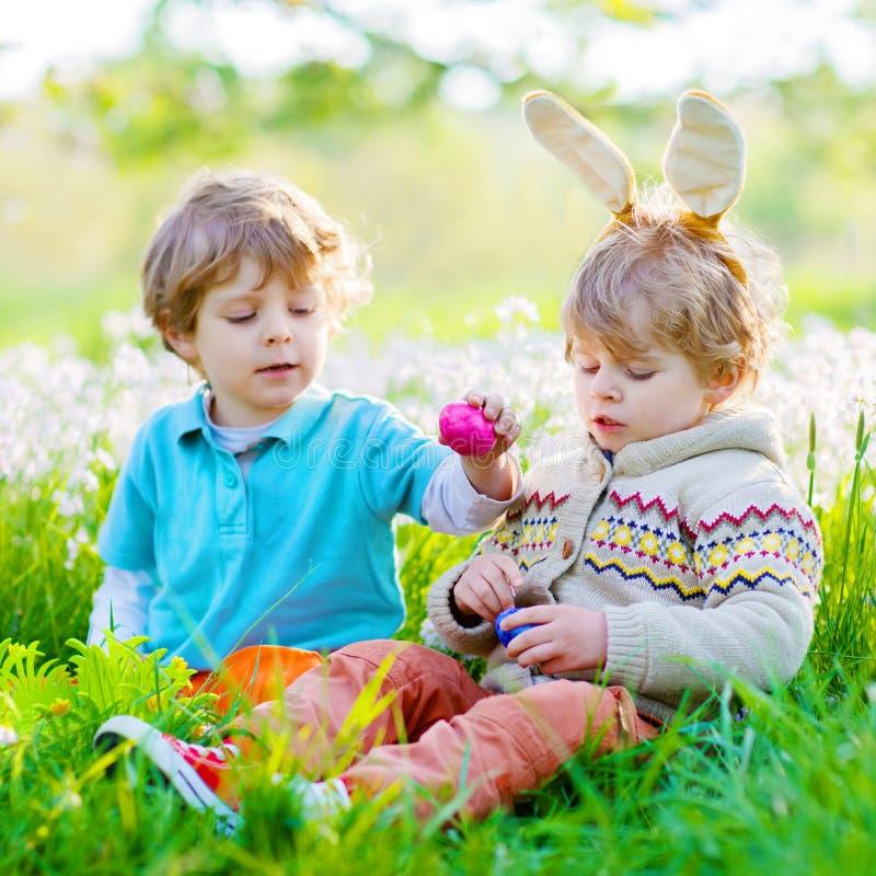 Zwei Kleinkindjungen und -freunde in den Osterhasenohren während des traditionellen Eies jagen im Frühjahr Garten, draußen geschw stockfotos