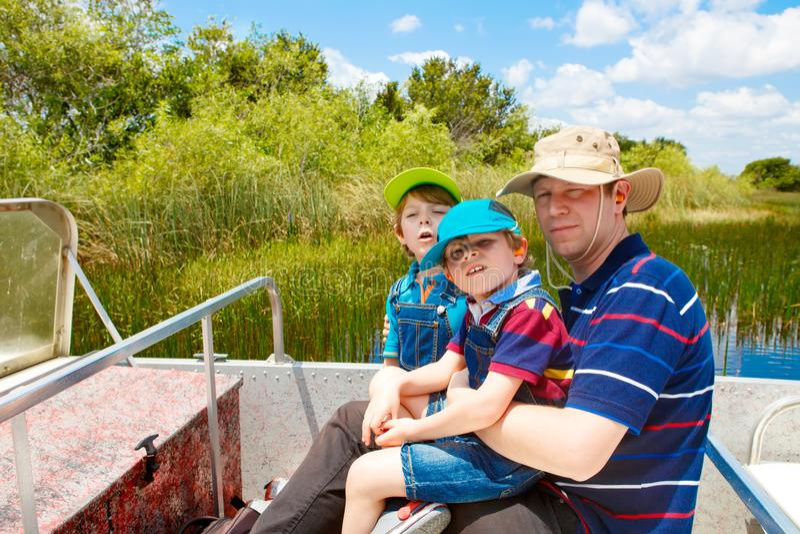 Zwei Kleinkindjungen und -vater, die Luft Boot herstellen, in Everglad zu bereisen stockfotografie