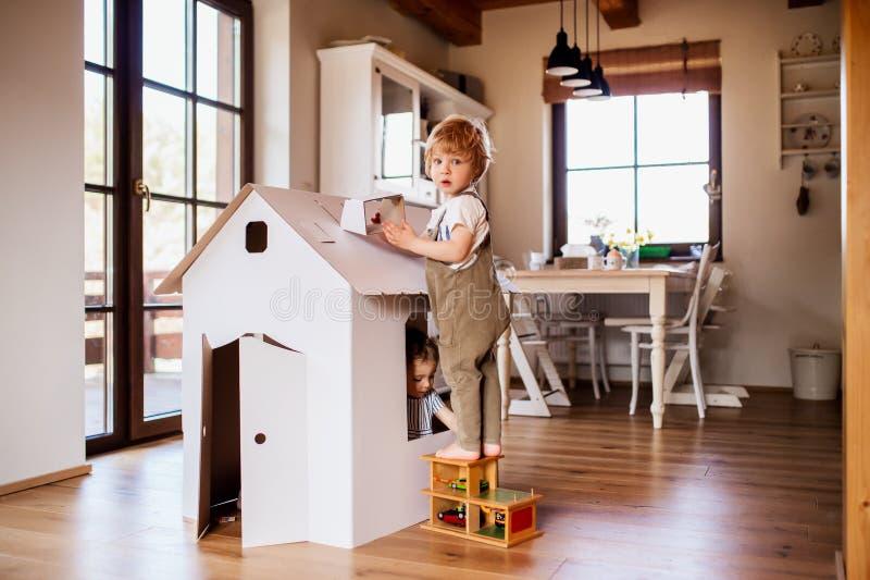 Zwei Kleinkindkinder, die zuhause mit einem Kartonpapierhaus zu Hause spielen lizenzfreie stockfotos