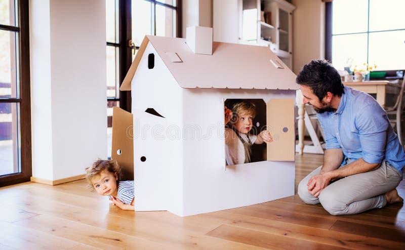 Zwei Kleinkindkinder mit dem Vater, der zuhause mit Papierhaus zu Hause spielt lizenzfreie stockfotografie