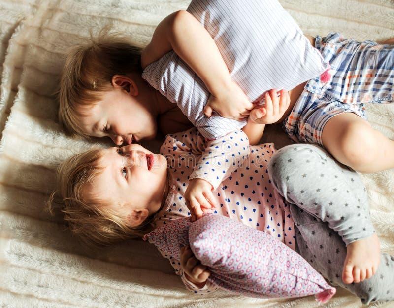 Zwei Kleinkindlügen auf dem Bett stockfotografie