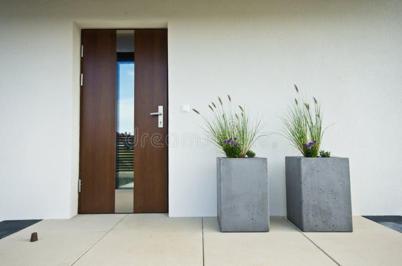 Zwei konkrete Blumenkubiktöpfe an der Haustür eines Hauses lizenzfreies stockfoto