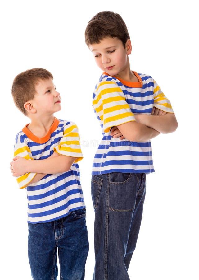 Zwei kontroverse Jungen, die zusammen auf weißem Hintergrund stehen lizenzfreies stockbild