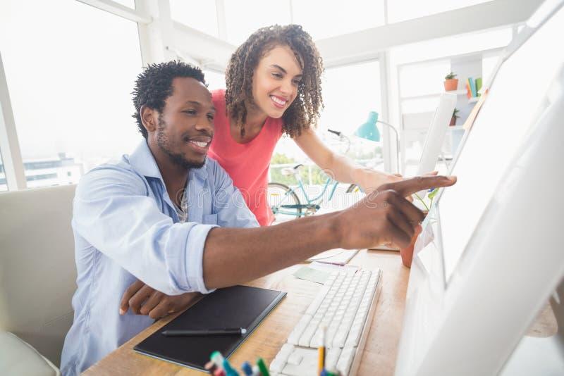 Zwei kreative Geschäftskollegen, die den Computer aufpassen stockfotografie