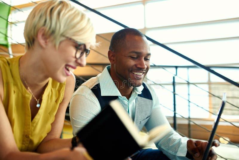 Zwei kreative millenial Kleinunternehmer, die an Social Media-Strategie unter Verwendung einer digitalen Tablette beim herein sit stockfotos