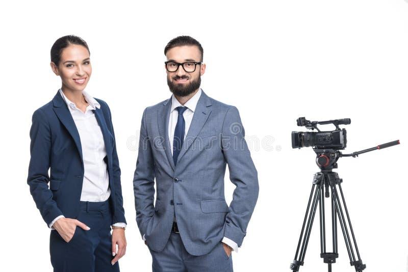 zwei lächelnde Ansager, die nahe Fernsehvideokamera stehen, stockfoto