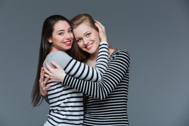 Zwei lächelnde attraktive junge stehende und umarmende Frauen lizenzfreies stockfoto
