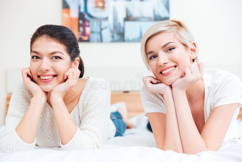 Zwei lächelnde Frauen, die auf dem Bett liegen stockbild