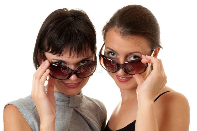 Zwei lächelnde Frauen mit Gläsern lizenzfreie stockfotos