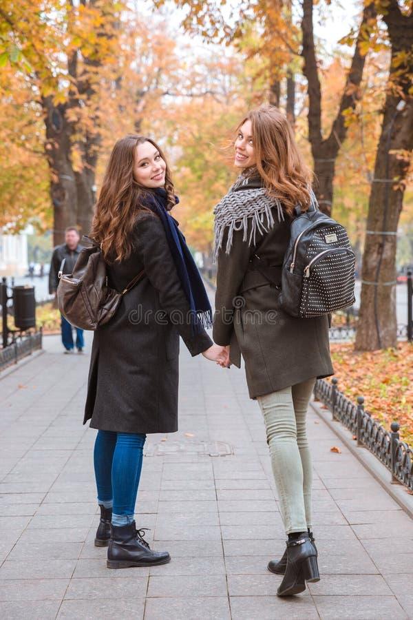 Zwei lächelnde Freundinnen, die in Herbstpark gehen lizenzfreie stockfotografie