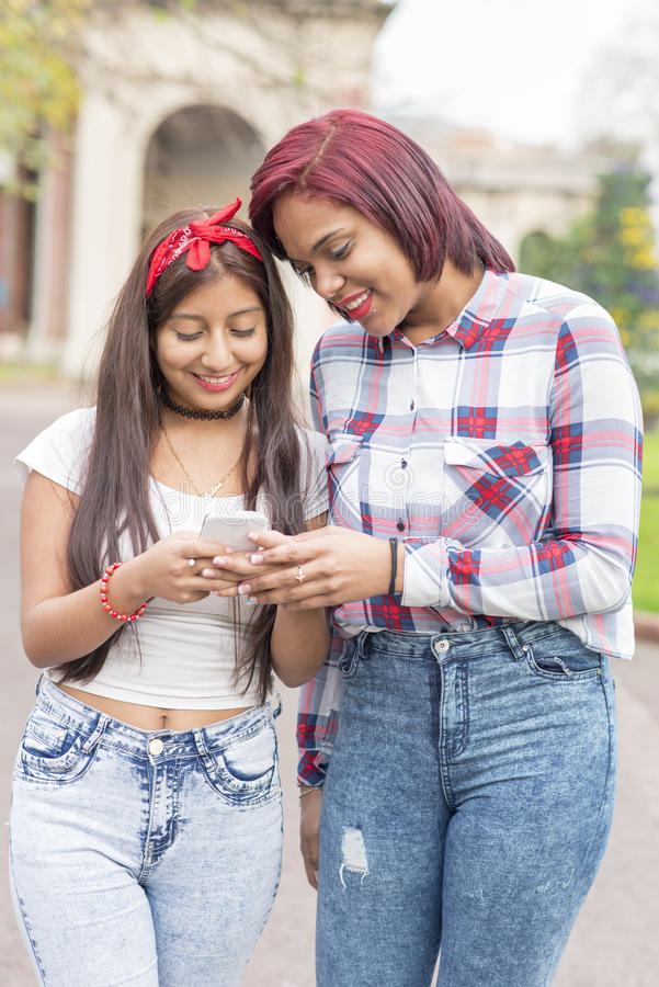 Zwei lächelnde Freundinnen, die Social Media in einem intelligenten Telefon teilen stockfotografie