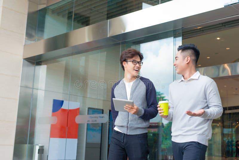 Zwei lächelnde Geschäftsmänner, die in der Stadt gehen und sprechen lizenzfreie stockbilder