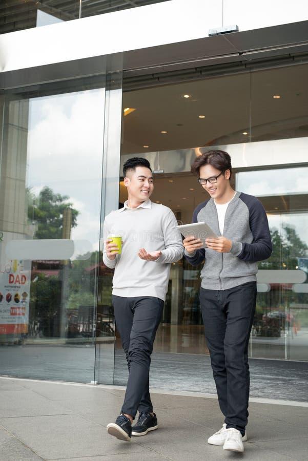 Zwei lächelnde Geschäftsmänner, die in der Stadt gehen und sprechen lizenzfreies stockfoto