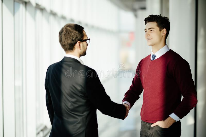 Zwei lächelnde Geschäftsmänner, die zusammen Hände beim Bereitstehen von Fenstern in einem Bürositzungssaal übersieht die Stadt r stockfoto