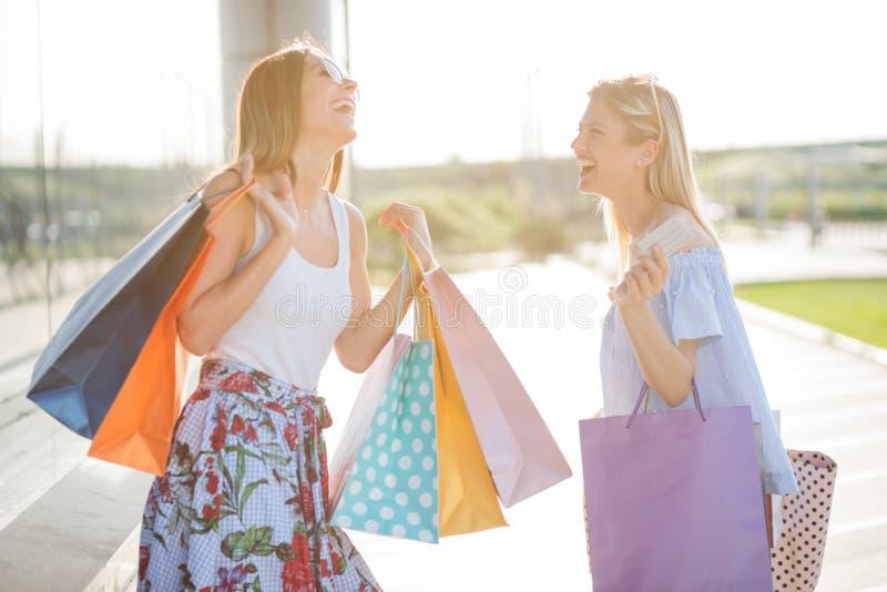 Zwei lächelnde glückliche junge Frauen, die vom Einkaufen zurückkommen lizenzfreies stockfoto