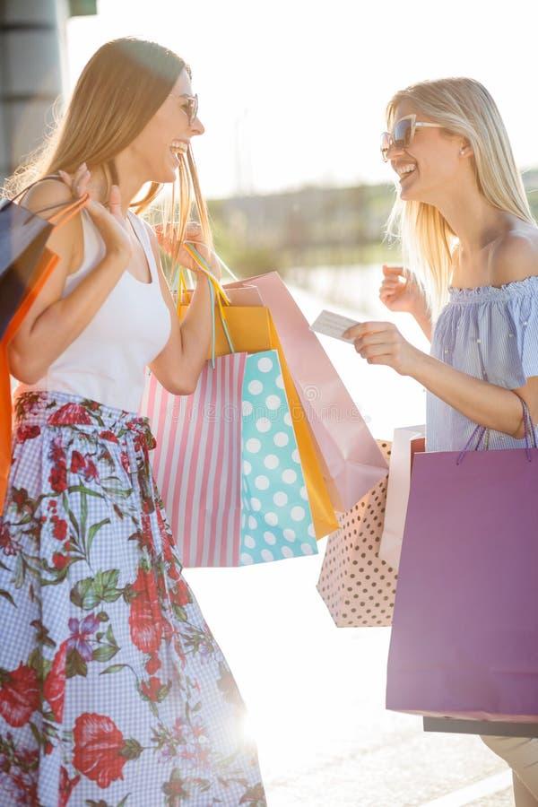 Zwei lächelnde glückliche junge Frauen, die vom Einkaufen zurückkommen lizenzfreies stockbild