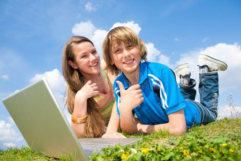 Zwei lächelnde Jugendliche mit Laptop stockfotos