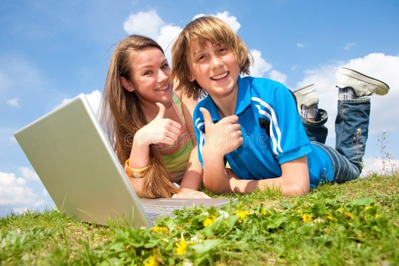 Zwei lächelnde Jugendliche mit Laptop lizenzfreie stockfotos