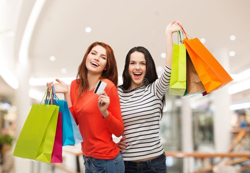 Zwei lächelnde Jugendlichen mit Einkaufstaschen stockfotos
