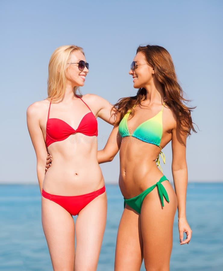 Zwei lächelnde junge Frauen auf Strand lizenzfreie stockbilder
