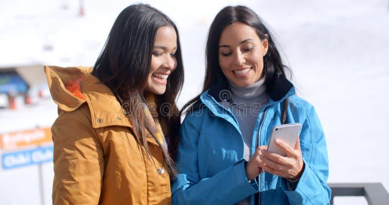Zwei lächelnde junge Frauen, die ein Telefon überprüfen stockfotos