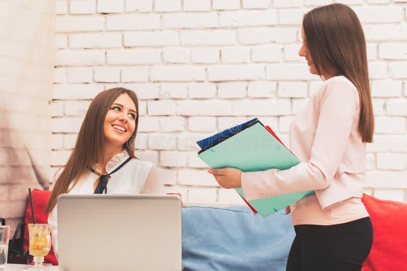 Zwei lächelnde junge Frauen in einem Geschäftstreffen stockbild