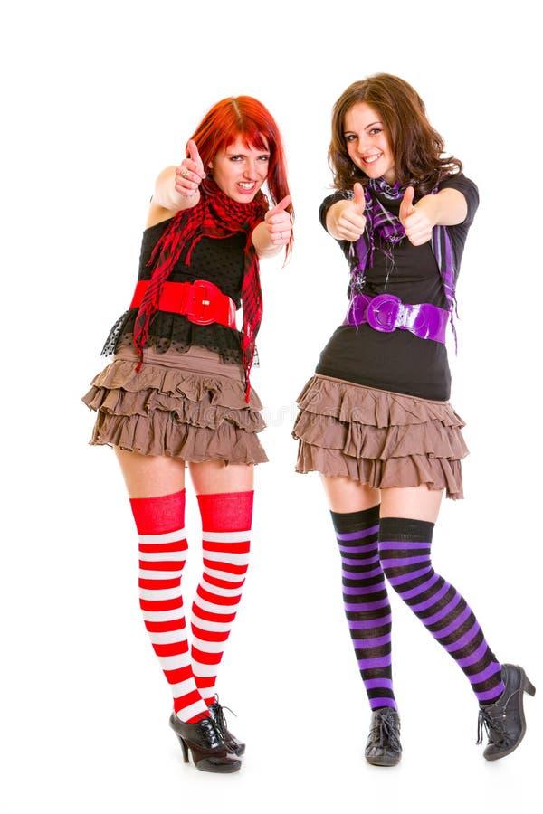 Zwei lächelnde junge Freundinnen, die sich Daumen zeigen stockbild