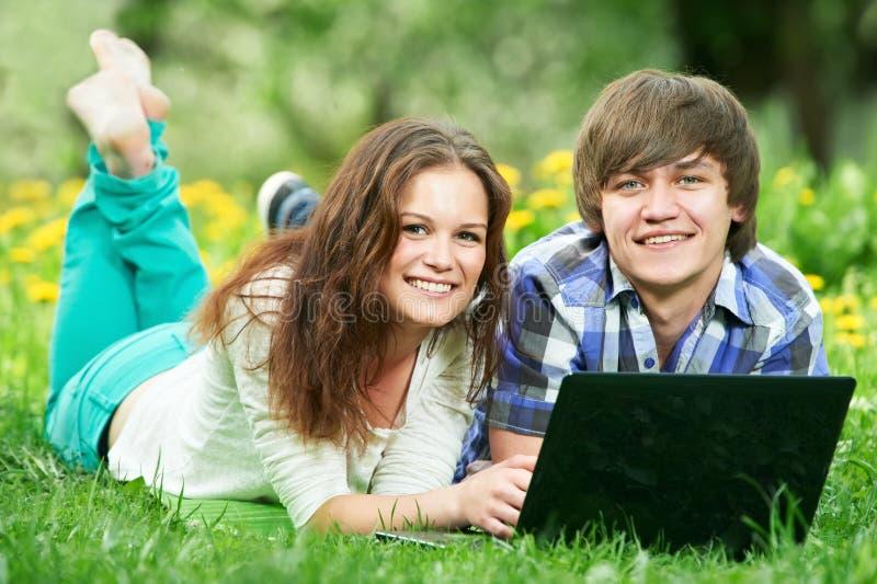 Zwei lächelnde junge Kursteilnehmer draußen mit Computer lizenzfreies stockfoto