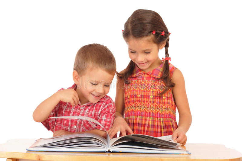 Zwei lächelnde Kinder, die das Buch auf dem Schreibtisch lesen lizenzfreies stockfoto