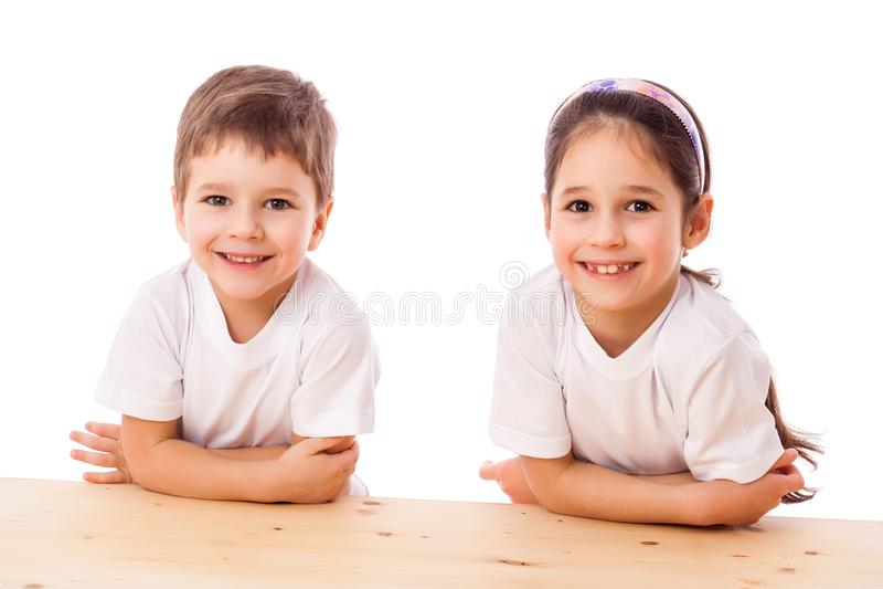 Zwei lächelnde Kinder am Schreibtisch stockfoto