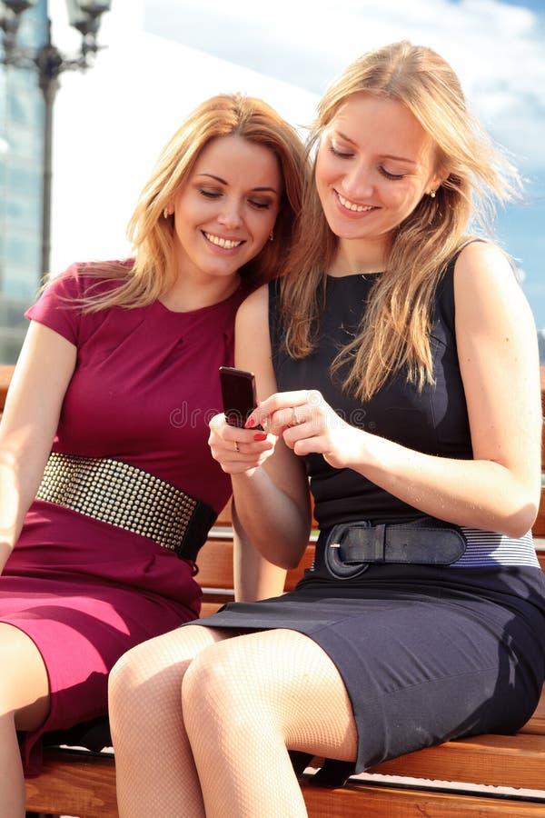 Zwei lächelnde Mädchen mit einem Telefon stockbild