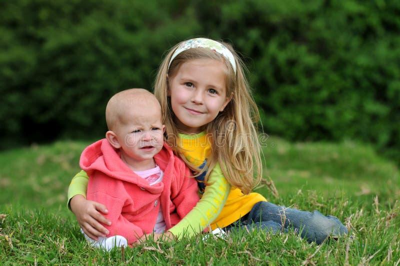 Zwei lächelnde Schwestern auf dem Rasen stockfotografie