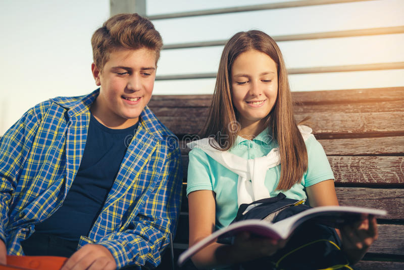 Zwei lächelnde Studenten mit ihrem Studieren der Taschen in der Schule, im Freien lizenzfreie stockbilder