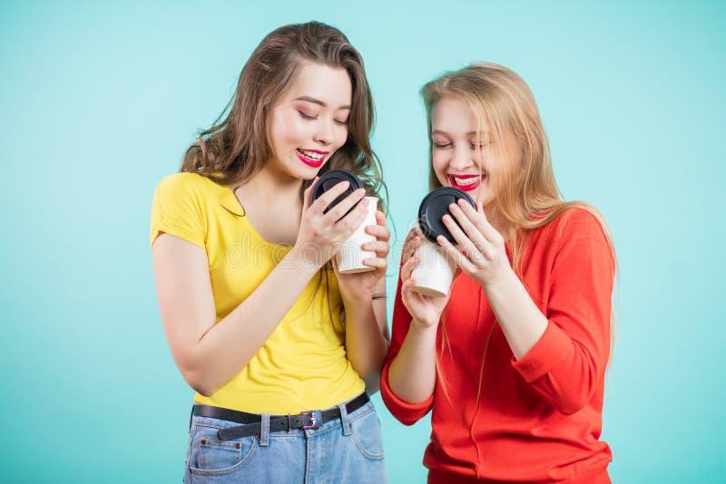 Zwei lächelnde Studentenmädchen, die Morgenkaffee trinken, inhalieren das Aroma des Kaffees lizenzfreies stockfoto