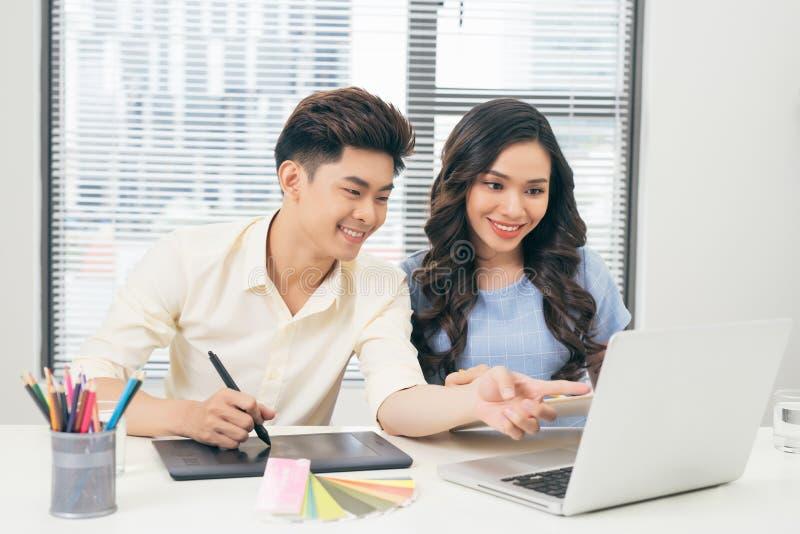 Zwei lächelnde zufällige Designer, die mit Laptop beim Sitzen von a arbeiten lizenzfreie stockfotos
