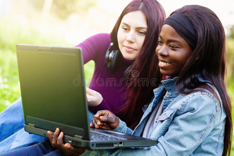 Zwei l?chelnde junge M?dchen unter Verwendung des Laptops am Park stockbild