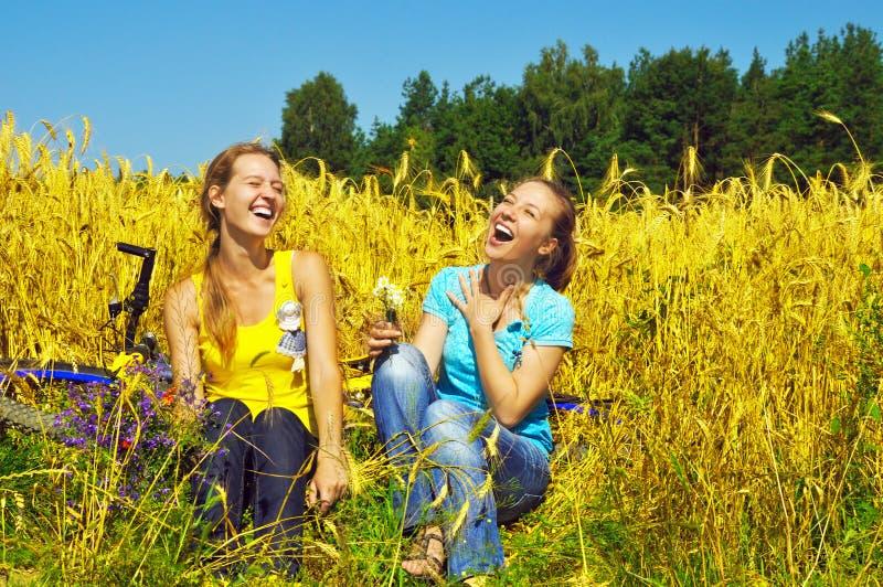 Zwei lachende hübsche Mädchen stehen auf dem goldenen Gebiet still lizenzfreies stockfoto