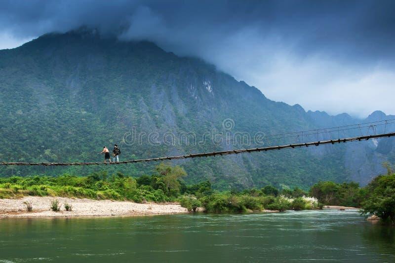 Zwei Laos-Mädchen, die über die Hängebrücke über dem Nam Song River, fantastischen bewölkten und Gebirgszughintergrund gehen stockbilder