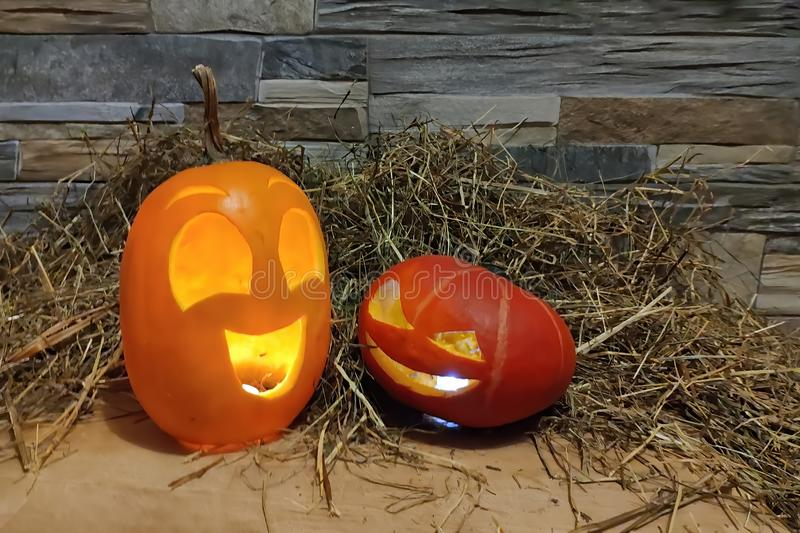 Zwei Laternen Halloween-Steckfassung O gelb und rot auf einem Heu- und Backsteinmauerhintergrund lizenzfreie stockfotos