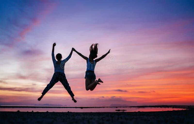 Zwei laufend und springende Freundinnen auf dem Sonnenuntergangseestrand Hand in Hand Konzeptbild stockbilder
