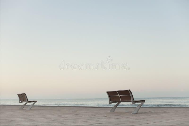 Zwei leere Bänke durch das Meer lizenzfreies stockfoto