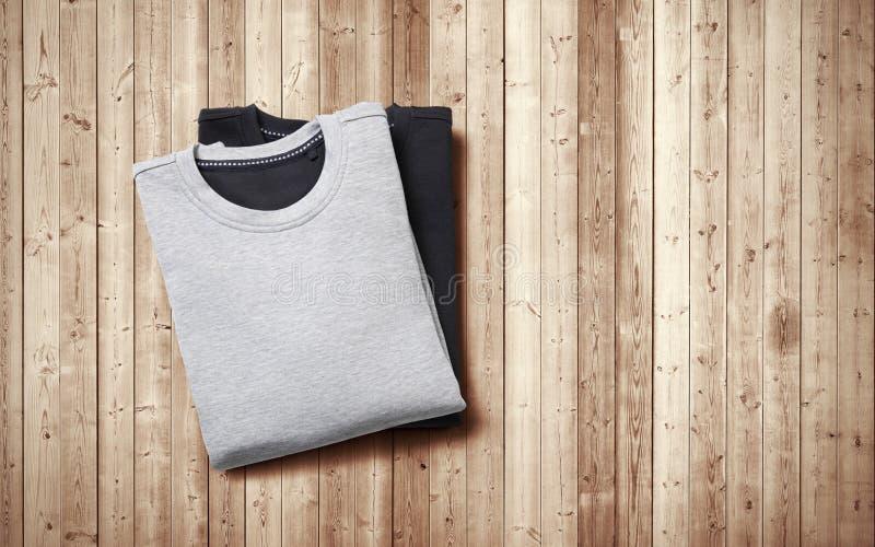 Zwei leere Pullover, die auf hölzernem Hintergrund liegen stockbilder