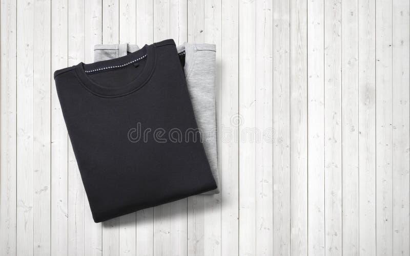 Zwei leere Pullover, die auf weißem hölzernem Hintergrund liegen lizenzfreie stockbilder