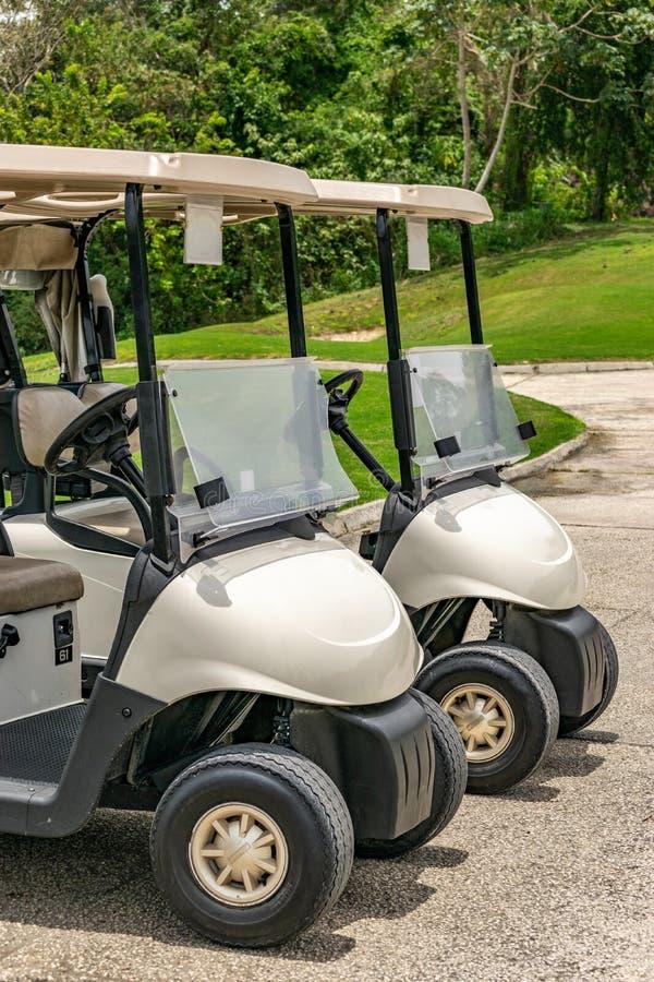 Zwei leere wei?e Golfmobile nebeneinander geparkt lizenzfreies stockbild