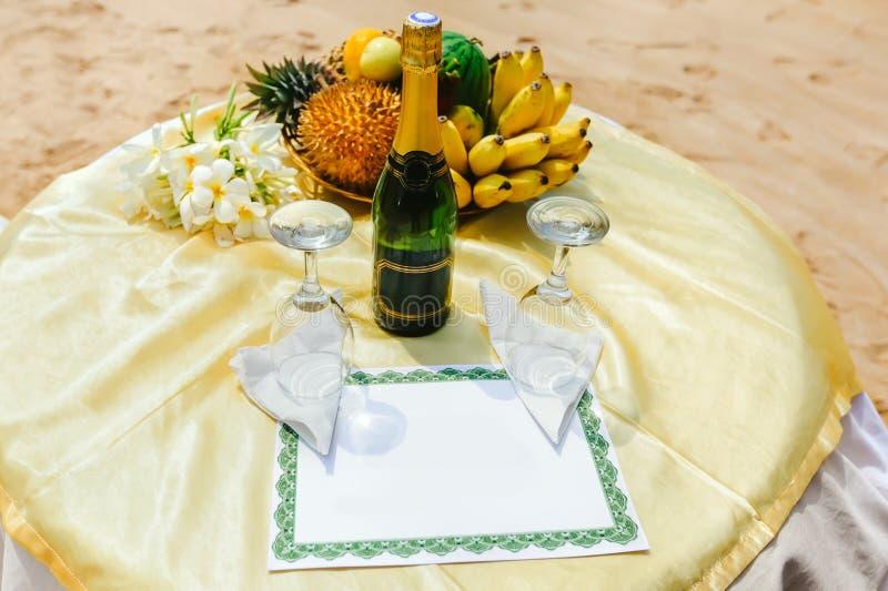 Zwei leere Weingläser nahe bei einer Flasche Champagner auf dem Tisch lizenzfreies stockbild