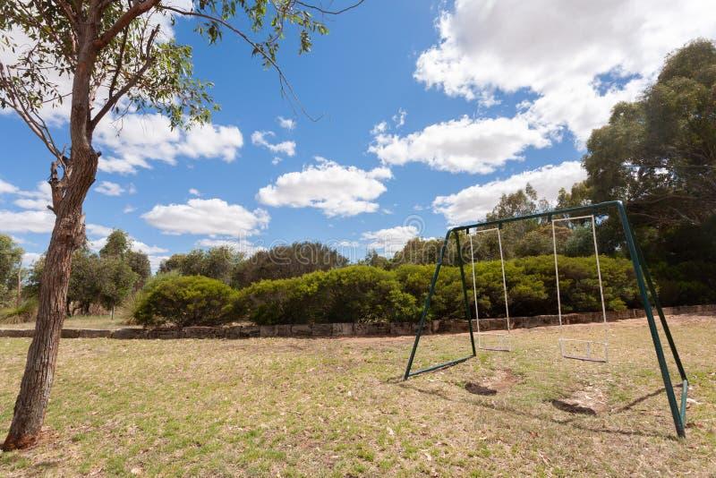Zwei leeres Schwingen auf Gras mit einem kleinen Baum im Vordergrund unter einem blauen Himmel mit einigen weißen Wolken lizenzfreies stockfoto