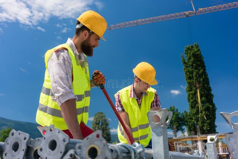 Zwei leistungsfähige Arbeitskräfte, die ein metallisches Gestell errichten lizenzfreies stockfoto