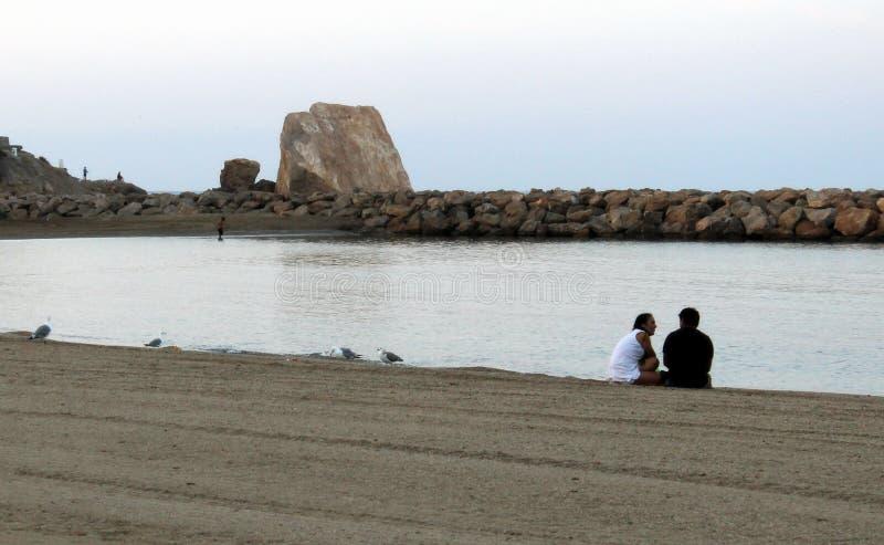 Zwei Leute, die auf Sand sitzen und sehr nah miteinander nahe bei der Küste sprechen stockfoto